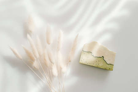 Handmade soap and dried bunny tail grass. Sunshade shadow on white background. Zero waste, eco friendly cosmetics concept. Vintage color filter
