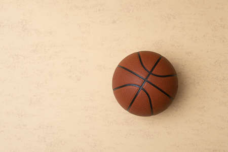 Close up of brown basketball ball isolated on beige background. Sport team concept. Top view, space for your text 免版税图像