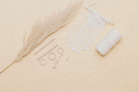 Macrame accessories on beige background. Creative hobby concept. Top view. Vintage color filter