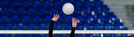 Girl Volleyball player and setter setting the ball for a spiker during a game. Professional sport concept