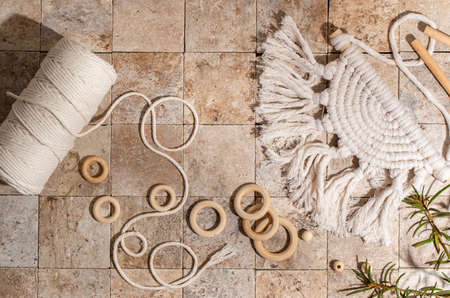Macrame accessories on beige background. Creative hobby concept. Top view
