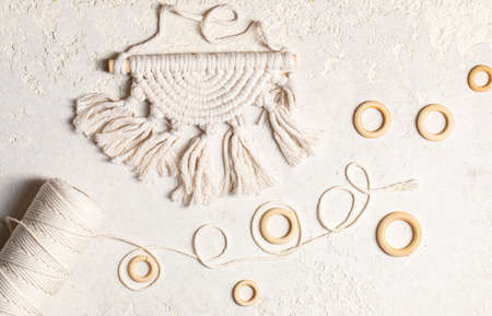 Macrame accessories on white concrete background. Creative hobby concept. Top view