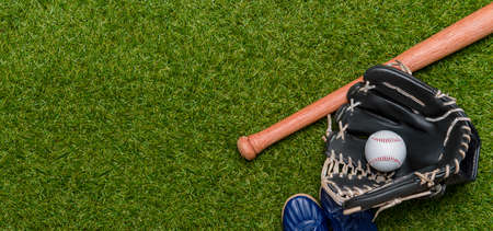 Baseball bat, shoes, glove and ball on green grass field. Sport theme background with copy space for text and advertisment Archivio Fotografico
