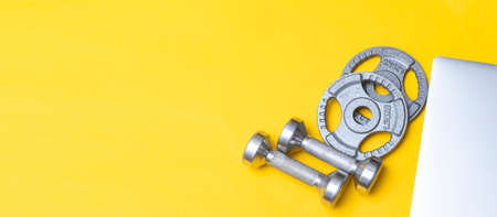 Silver dumbbells and  grey laptop on yellow background. Workout online home Archivio Fotografico