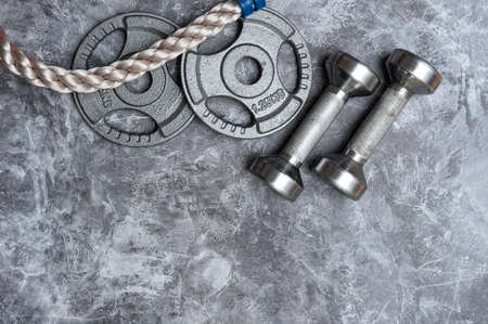 Close up of battle rope  and dumbbells on a gray backgound. Sport and fitness equipment. Functional training