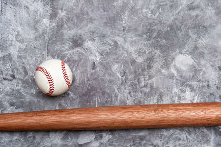 Baseball ball and bat on grey background. Team sport concept