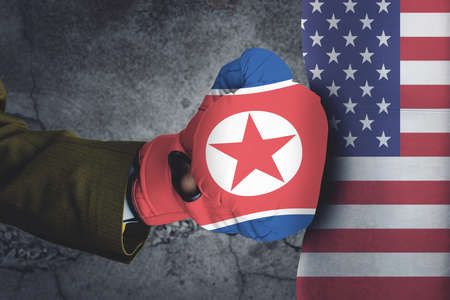 Conflict, close up of two fists hitting each other over dramatic concreate background , USA and North Korea conflict concept