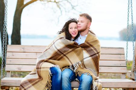 Amorous couple on romantic date on swings outdoor ,autumn Stock Photo