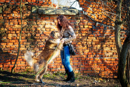 Young woman playing with Caucasian shepherd in a delightful spring day