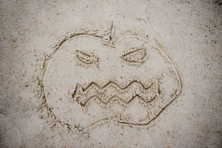 Helovinskoho pumpkin symbol drawn in the sand on a cloudy autumn day Stock Photo