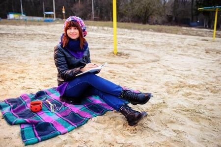 sit down: Hermosa chica sentada en la playa y tiene registros en un cuaderno