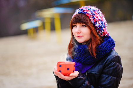 woman drinking coffee from her thermos, enjoying autumn evening by the sea Stock Photo
