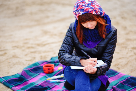 beautiful girl sitting on the beach and has records in a notebook, the appearance of the shoulder