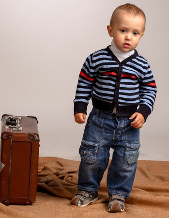 Two, three years old baby boy carry big suitcase isolated on a white background. transportation, moving, journey concept.