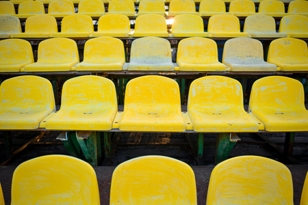old yellow seat in stadium closeup, background