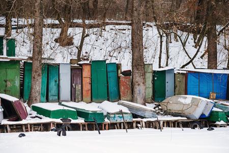 Winter landscape with fisherman boats lying on frozen lake shore. Winter lake landscape