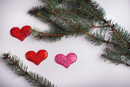 Wooden white background with a branch of pine and three hearts. The concept for Valentines Day