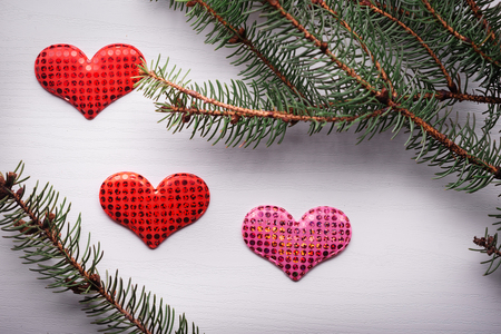 heartshaped: Wooden white background with a branch of pine and three hearts. The concept for Valentines Day