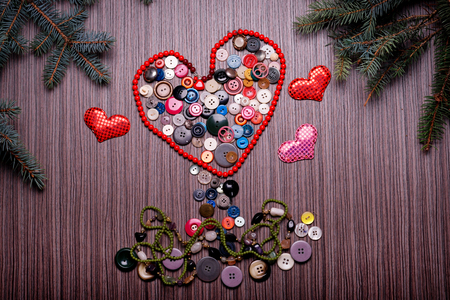 Heart for Valentines Day composed of buttons on dark board Stock Photo