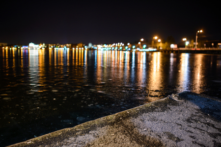 Frozen lake on the background of the city at night and the roads