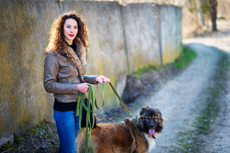 sitter: Young woman playing with Caucasian shepherd in a delightful spring day