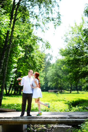 The bride and groom in the Park.A pair of newlyweds, the bride and groom at the wedding in the green forest nature kiss photo. Stock Photo