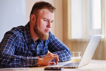 Young man working on laptop at home. Stock Photo