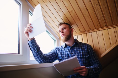 work from home: Businessman at home, he is working with of paper. Stock Photo