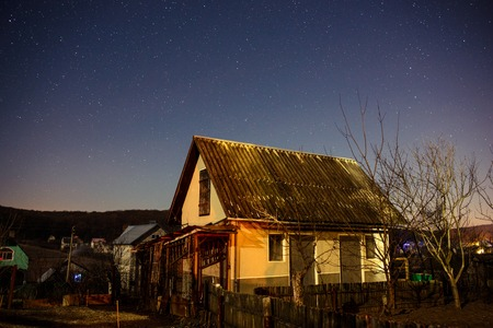 starry night: wooden house on a background of the night sky.