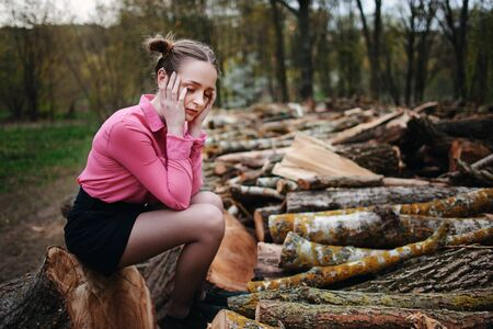 fallen tree: Beautiful young woman sitting on stack of felled tree trunks in the forest.
