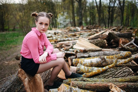 Beautiful young woman sitting on stack of felled tree trunks in the forest.