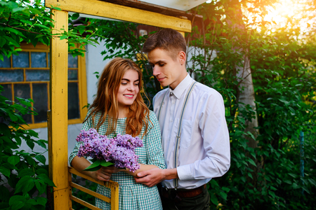 guy gives his girlfriend a bouquet of lilacs.