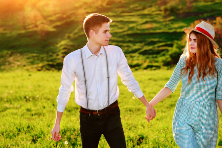 arm bouquet: A young man walks with his girlfriend in the park.