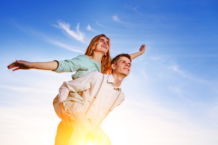 reggicalze: Young guy piggybacking cheerful girlfriend like airplane on the background of sky. Archivio Fotografico