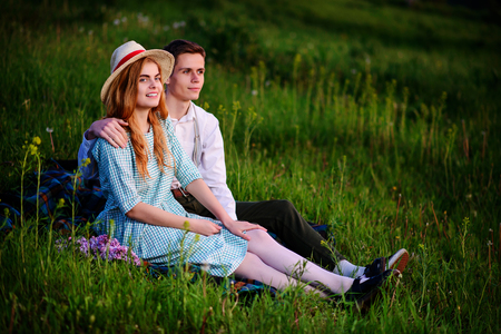 young couple sitting on the plaid in the park and look at the sunset. Stock Photo