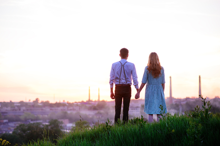 daybreak: young couple is holding hands on a background sunset.