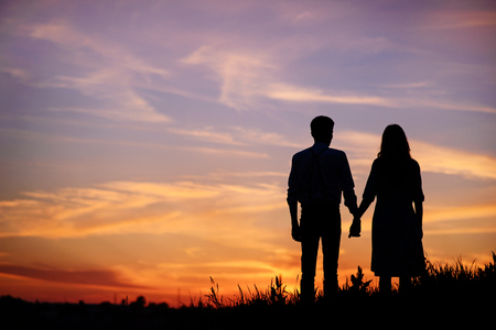 young couple is holding hands on a background sunset silhouette. Stock Photo