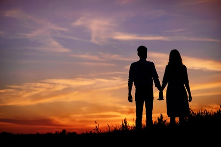 daybreak: young couple is holding hands on a background sunset silhouette. Stock Photo