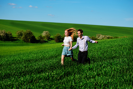 Young happy lovers running on meadow with green grass and blue sky. Stock Photo