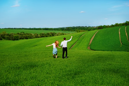 Young happy lovers running on meadow with green grass and blue sky, From the back. Stock Photo