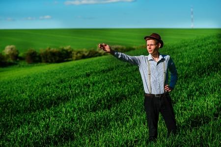 De man op het veld vertoont ergens ver in iets op een langwerpige hand.