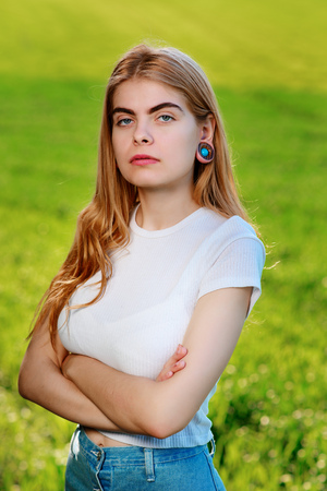Portrait of a young beautiful woman with wooden tunnels in her ears.