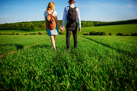 With a backpack, a man in a hat and a woman with long hair go along the path. A couple walks along the meadow.