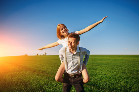 Smiling Man is holding on his back happy woman, who pulls out her arms and simulates a flight against the background of the blue sky and the green field.