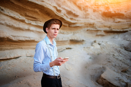 sand quarry: An attractive man looking at the screen of a smartphone on the background of a sand quarry.