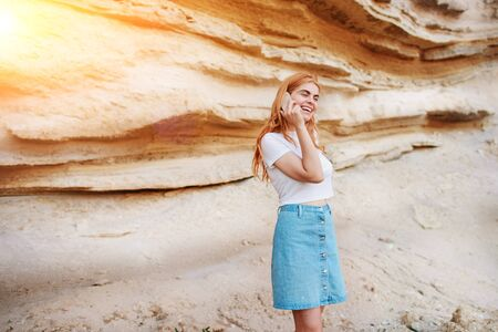 A beautiful woman is smiling and talking by smartphone on the background of a sand quarry. Stock Photo