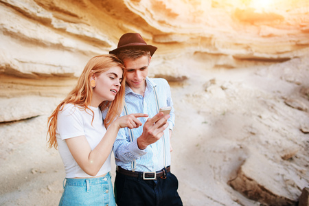 sand quarry: Attractive man and beautiful woman are looking at the screen of a smartphone on the background of a sand quarry. Stock Photo