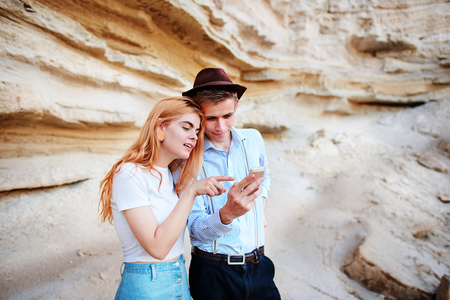 Attractive man and beautiful woman are looking at the screen of a smartphone on the background of a sand quarry. Stock Photo