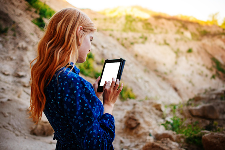 Woman looking at the screen of a tablet on the background of a sand quarry. Stock Photo