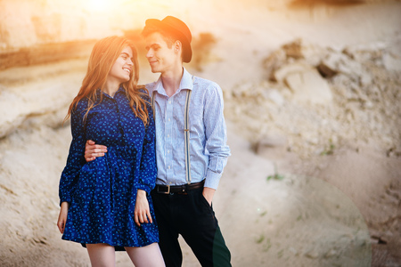 An attractive man hugs a beautiful woman. The pair wrapped in plaid in the middle of a sandy canyon. Stock Photo